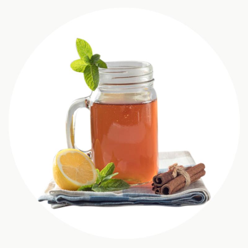Kombucha natural y bio servida en jarra de vidrio con limón, menta y canela